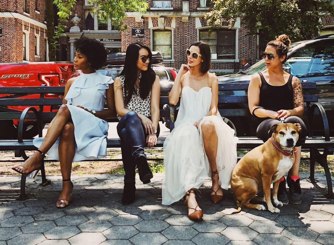 個性的な女性4人がベンチに座り犬が1匹座っている